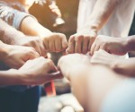 Close up of young people putting their hands together. Team with stack of hands showing unity and teamwork.